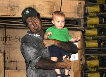 "Black with bone and holding plant production Manager Jeff Booms' son, Colin, is ""Dirty Jobs"" host Mike Rowe at Ebonex Corp. in Melvindale. The company specializes in using charred animal bones to create other products. (Photo courtesy of Ebonex Corp.)"